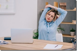 Businesswoman Stretching Shoulders At Workplace In Office